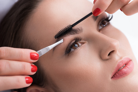 tweezing eyebrow: Close up of cosmetician hands pulling out female eyebrows by tweezers and combing it by brush. Young woman is looking forward with tranquility