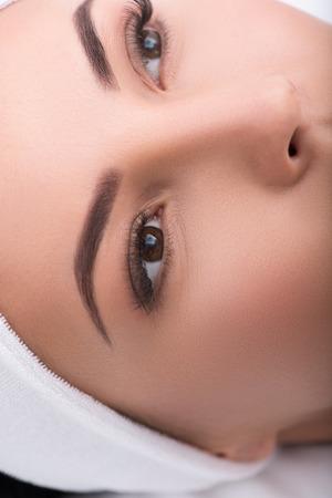 Cierre de ojos femeninos con pestañas artificiales. Calma joven está mintiendo y relajante en el salón de belleza Foto de archivo