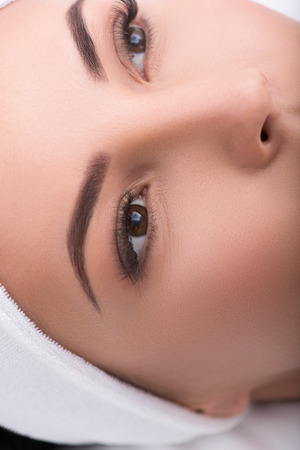 Close up of female eyes with artificial lashes. Calm young woman is lying and relaxing at beauty salon Stock Photo