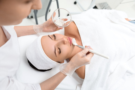cosmetician: Experienced cosmetician is applying healthy clay on female chin. Girl is lying and relaxing. Her eyes are closed with pleasure
