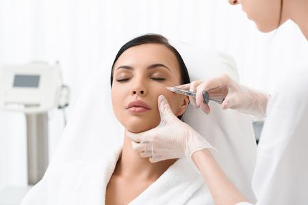 De mooie jonge vrouw geeft om haar huid op schoonheidsspecialistenbureau. Ze zit en krijgt botoxinjectie. Haar ogen zijn gesloten met kalmte