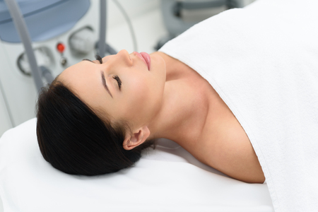 regeneration: Healthy young woman is sleeping on bed at spa salon. She is lying near equipment