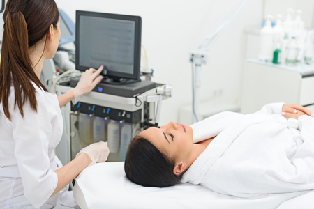 Professional beautician is preparing equipment for cavitation procedure at clinic. Young woman is lying on table with relaxation