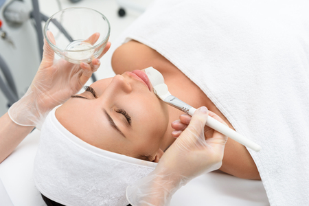 Pretty young woman is getting skin care treatment at spa. She is lying with enjoyment. Beautician is applying clay on her face