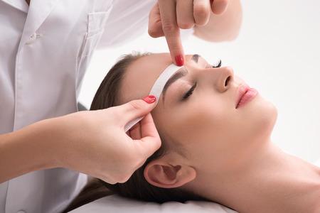 Ruhiges junges Mädchen, das Epilation der Augenbraue erhält. Kosmetikerin wendet Wachspapierstab auf Haar an Standard-Bild - 64894910