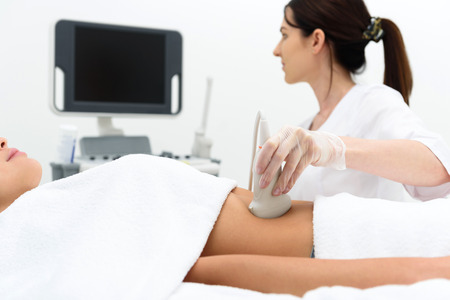 general practitioner: Experienced general practitioner is examining female abdomen by ultrasound equipment. She is sitting and looking at monitor with concentration