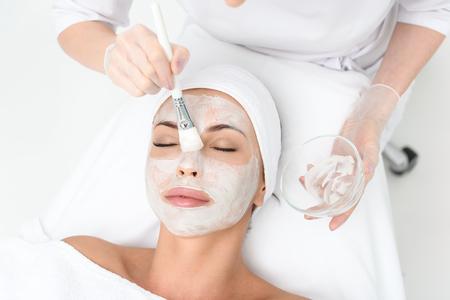 Vista superior de primer plano de los brazos cosmetólogo que aplican la crema en la cara femenina. Ella está sosteniendo el cepillo y el cuenco. La mujer joven está mintiendo y descansando. Tiene los ojos cerrados de placer Foto de archivo - 64894919