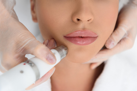 chin on hands: Top view close-up of beautician hands making ultrasound facial procedure. She is touching woman chin with laser