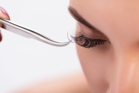 Close up of female eye getting lash extension. Tweezers sticking lash to eyelid Stok Fotoğraf