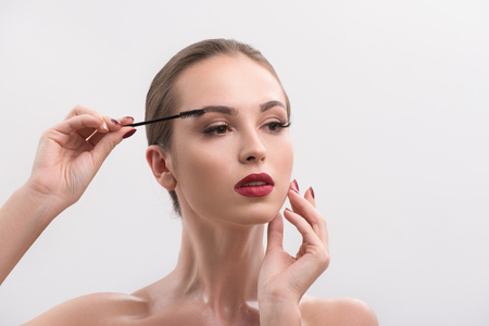 Sensual young woman is combing her eyebrows by brush. She is standing and touching her face with pleasure. Isolated and copy space in right side