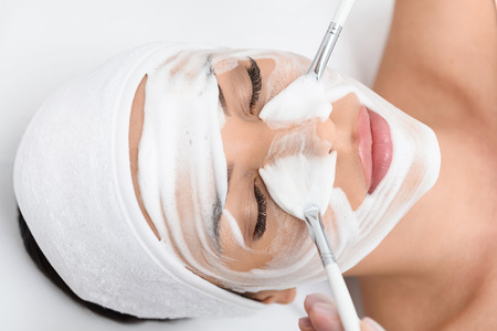 Draufsichtnahaufnahme des Gesichtes der jungen Frau, das am Badekurortsalon liegt und sich entspannt. Kosmetiker trägt Creme auf Haut durch zwei Bürsten auf Standard-Bild - 64894952
