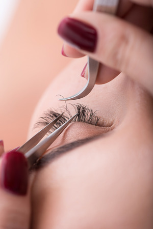 Close up of beautician hands is sticking artificial eyelash to female eye by tweezers Stock Photo