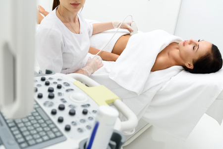 Pregnant woman is visiting gynecologist at clinic. She is lying and getting ultrasound abdomen examination. Doctor is sitting and looking at monitor with seriousness