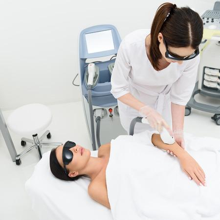 mimos: mujer joven y sana está mintiendo y relajante en mesa de masaje en el salón de belleza. Esteticista está mimando a su lado por el equipo de cuidado de la piel con láser con la concentración. Se trata de llevar gafas protectoras