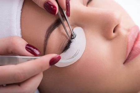 makeup eyes: Skillful beautician is undergoing eyelash extension procedure. Close up of female face Stock Photo