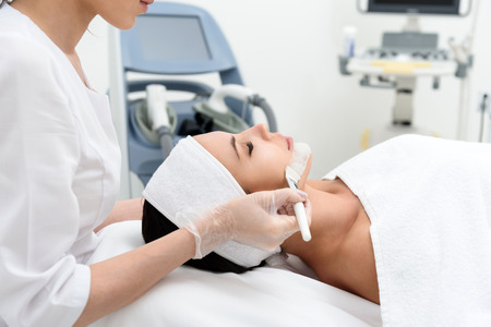 cosmetician: Skillful cosmetician is making healthy facial mask for client. She is standing and touching brush to female chin. Young woman is lying with closed eyes and relaxing