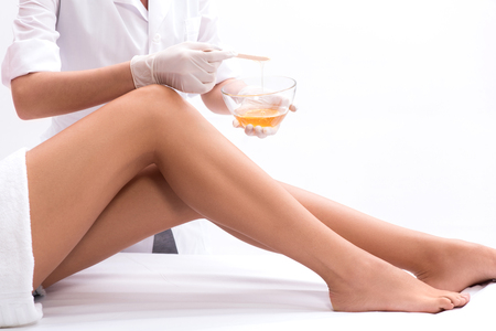 Professional beautician is applying wax on female legs to remove hair Stok Fotoğraf