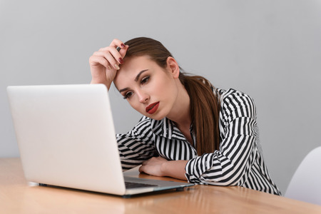 unmotivated: Young woman is tired from work. She is sitting at desk and looking at laptop with boredom Stock Photo