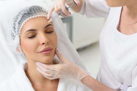 穏やかな若い女性は、彼女の額にボトックス注射をなっています。彼女が医者のオフィスで座っているとリラックス