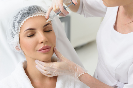 Serene young woman is getting botox injection into her forehead. She is sitting in doctor office and relaxing 스톡 콘텐츠