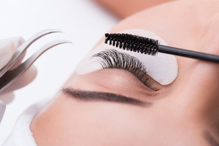 Close up of eyelash extension procedure. Tighten up brush and tweezers near female eye