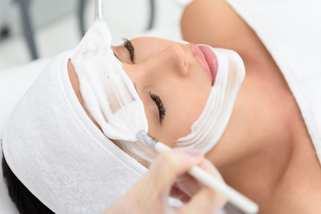 Close up of female face with cosmetic mask. Beautician is applying foam on her forehead by brushes Stock Photo