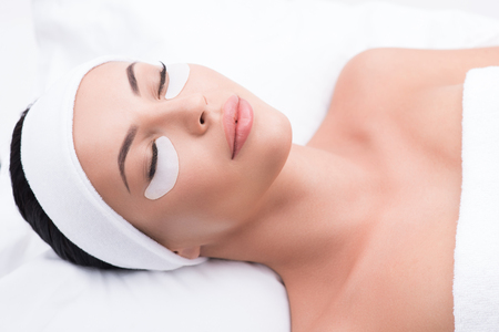 Relaxed young woman is having eyelash extension procedure. She is lying and closed eyes with enjoyment