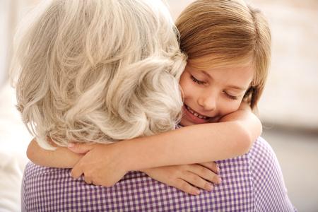 다정한 손녀와 할머니는 포옹을하고 있습니다. 소녀는 눈을 감고 미소를 지었다.