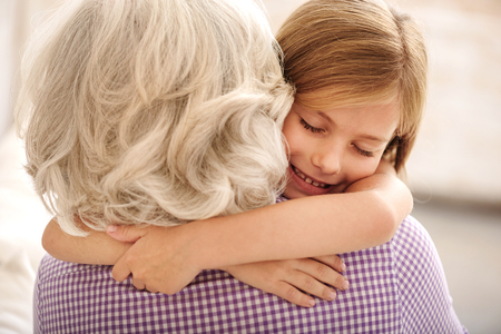 Affectionate granddaughter and grandmother are hugging. Girl is smiling with closed eyes