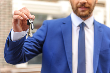 accommodation broker: keys in hand of a bearded man in uniform, selective focus Stock Photo