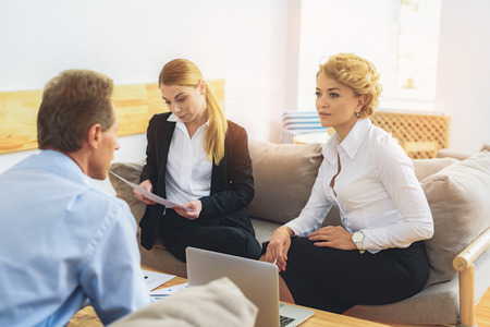 seriousness: Business team is discussing project at office. They are sitting on couch and looking each other with inspiration. Woman is reading documents with seriousness Stock Photo