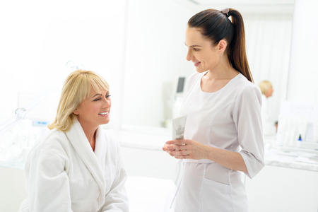 Confident beautician is advising new cream to senior woman. She is holding tube and smiling
