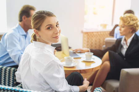 break: Colleagues are having coffee break in lounge office room. Young woman is looking at camera and smiling Stock Photo