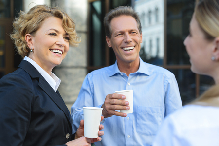 Sharing their impressions after meeting. Shot of adult coworkers having conversation during coffee break outdoor and smiling