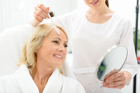 Joyful mature woman is sitting at beautician office and smiling. She is looking at mirror with excitement. Cosmetologist is touching her forehead with white pencil