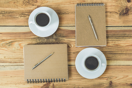 top veiw: Everything you need for meeting. Top veiw of wooden table with two kraft notebooks, two pens and two cups of coffee on it
