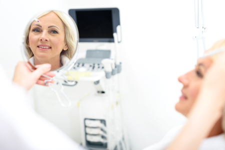 Joyful mature woman is looking at mirror with satisfaction and smiling. Beautician is touching white pencil to her face Stock Photo