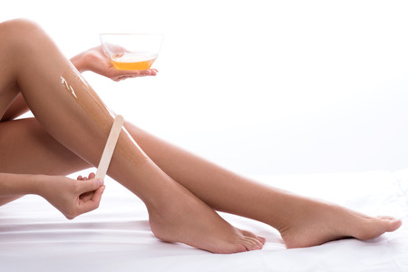 Preparation for beach season. Cropped photo of woman doing waxing depilation on her legs, isolated on white background Stock Photo - 64108715
