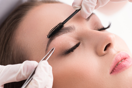 tweezing eyebrow: Plucking for perfection. Cropped shot of woman in white gloves using tweezers on patient eyebrow at health spa isolated on white background