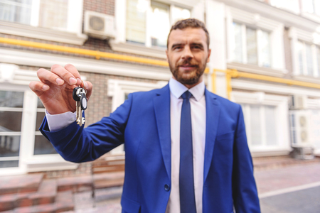 homeowner: you will be a homeowner, happy handsome realtor holding keys to the house in hands against buildings
