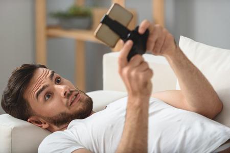 desilusion: Hombre que mira en la decepción teléfono con rabia Foto de archivo