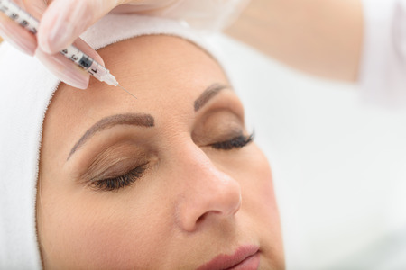 lift hands: Close up of senior woman face getting botox injection at clinic. Her eyes are closed with serenity Stock Photo