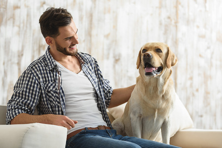 happy handsome man resting on a couch and petting his dog