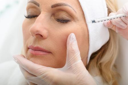 Cerca de la cara femenina madura que consigue la inyección de rejuvenecimiento por esteticista. La mujer se cerró los ojos con calma