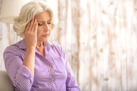 Mature woman suffers from headache at home. She is sitting and touching temples. Her eyes are closed with despair