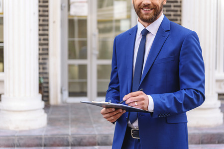 accommodation broker: bearded man in suit writing in a tablet outdoors, close up Stock Photo