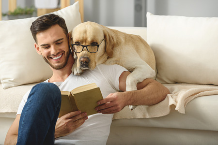 clever dog in glasses reading book with a bearded man Stok Fotoğraf