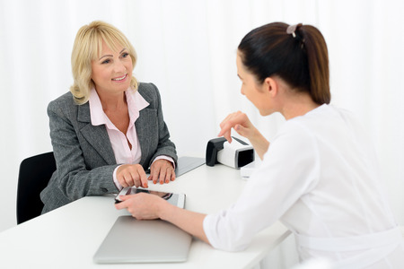 cosmetician: Professional cosmetologist is advising cosmetology procedure to senior woman. She is showing tablet to her. Mature lady is sitting and smiling Stock Photo