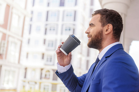 banker: smart banker holding a cup of beverage in the city with copy space