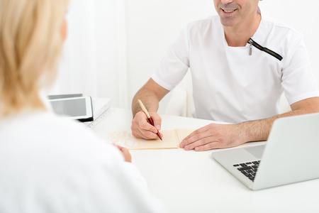 general practitioner: Experienced general practitioner is diagnosing mature woman. Man is sitting at desk and smiling Stock Photo